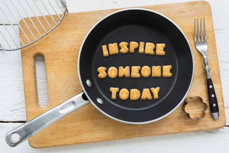 putting in: Top view of letter collage made of cookies. Quote INSPIRE SOMEONE TODAY putting in black pan. Other kitchen utensils: fork cookie cutter and cutting board putting on white wooden table vintage style image. Stock Photo