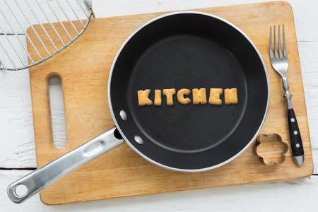 クッキーの文字のコラージュの平面図です。黒いパンに入れて単語キッチン。他の台所用品: フォークのクッキー カッターと白い木製テーブル ビン 写真素材