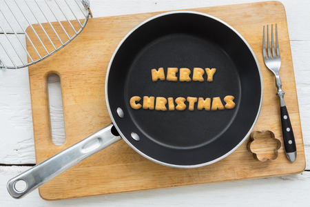 putting in: Top view of alphabet text collage made of cookies biscuits. Word MERRY CHRISTMAS putting in frying pan. Other utensils: fork cookie cutter and cutting board putting on white wooden table vintage style image.