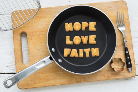 putting in: Top view of letter collage made of biscuits. Word HOPE LOVE FAITH putting in black frying pan. Other cooking equipments: fork cookie cutter and chopping board putting on white wooden table vintage style image.