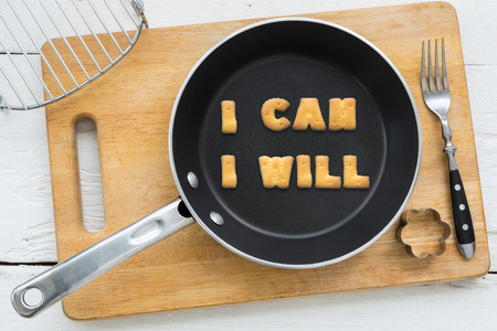 putting in: Top view of letter collage made of cookies. Quote I CAN I WILL putting in black pan. Other kitchen utensils: fork cookie cutter and cutting board putting on white wooden table vintage style image. Stock Photo
