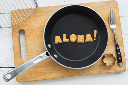 putting in: Top view of alphabet collage made of biscuits. Word ALOHA putting in black pan. Other kitchenware: fork cookie cutter and chopping board putting on white wooden table vintage style image.