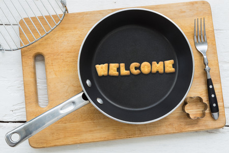 agreeable: Top view of alphabet text collage made of cookies biscuits. Word WELCOME putting in frying pan. Other utensils: fork cookie cutter and cutting board putting on white wooden table vintage style image. Stock Photo