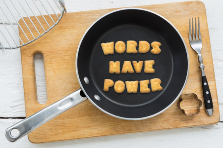 putting in: Top view of alphabet text collage made of cookies biscuits. Quote WORDS HAVE POWER putting in frying pan. Other utensils: fork cookie cutter and cutting board putting on white wooden table vintage style image.