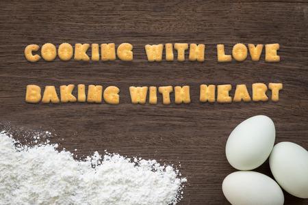 trompo de madera: Vista superior de collage de texto de la carta hecha de galletas galletas. COCINAR Cita con bicarbonato de amor con el corazón que pone en el fondo de horno con los huevos y la harina en la mesa de cocina de madera natural de la vendimia. Foto de archivo