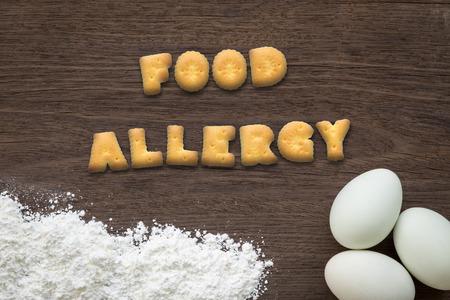 クッキー ビスケットの文字テキストのコラージュの平面図です。食物アレルギー卵と背景を焼くを入れての単語し、ヴィンテージ天然木製キッチン  写真素材