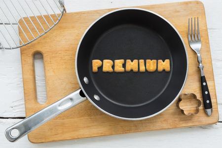 クッキーの文字のコラージュの平面図です。単語プレミアム黒鍋に置きます。他の台所用品: フォーク、クッキー カッター、白い木製のテーブル、