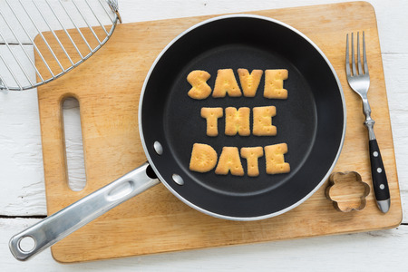 putting in: Top view of letter collage made of biscuits. Quote SAVE THE DATE putting in black frying pan. Other cooking equipments: fork, cookie cutter and chopping board putting on white wooden table, vintage style image. Stock Photo