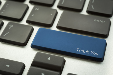 Close up computer keyboard focus on a blue button with typographic word THANK YOU. Online communication concept.