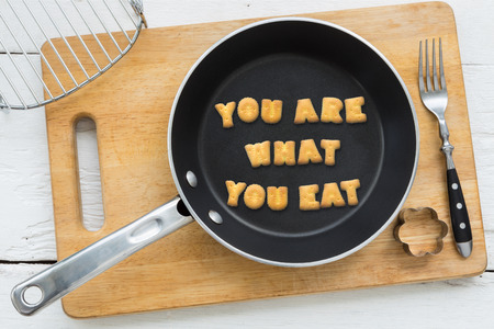 country life: Top view of letter collage made of biscuits. Quote YOU ARE WHAT YOU EAT putting in black frying pan. Other cooking equipments: fork, cookie cutter and chopping board putting on white wooden table, vintage style image. Stock Photo