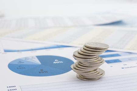 Geld-Symbol, Spirale Stapel von Silbermünzen setzen auf Papierkram, Charts und Datenanalyse.