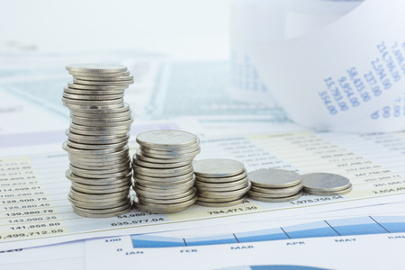Money symbol in curve. stacks of silver coins put on business financial statements and graphs. Stock fotó