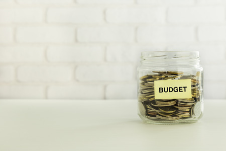 Coins in money glass jar with yellow BUDGET tag put on table, white bricks background. Annual funds, marketing plan, banking deposit  for insurance, education and retirement concepts. Stock Photo - 81020755