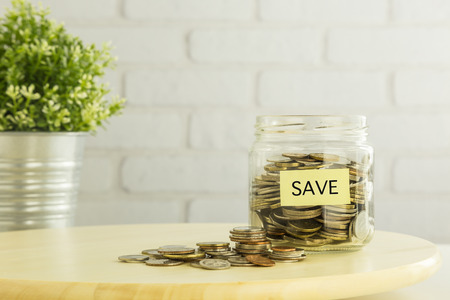intend: Coins in saving glass jar and on wooden table with yellow SAVE tag  and white bricks background. Save money for future financial planning, investment, education or retirement funds.