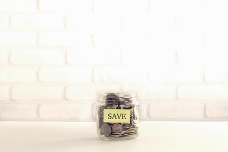 Gele SAVE-tag op het sparen van geldcontainer die vol is van wereldmunten, bakstenen achtergrond vintage retro stijl. Bespaar geld voor verzekering, donatie of bankdeposito.