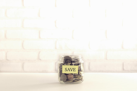 intend: Yellow SAVE tag on saving money container that full of world coins, bricks background vintage retro style. Save money for insurance, donation or bank deposit.