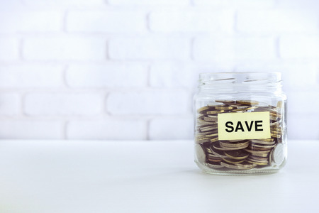 Yellow SAVE tag on saving money jar that full of world coins, bricks background vintage retro style.  Business strategies management, accounting and financial planning for save money.