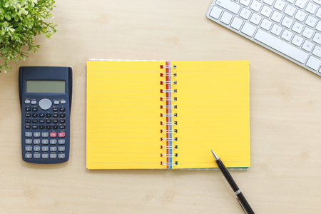 Top view of open book with yellow blank pages, calculator, modern keyboard, plants and black premium pen on workspace table background. Business management concept, minimal style.