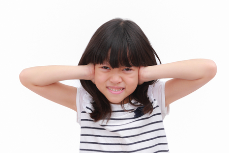 Asian kid girl express stress face and raise her hand close her ears. Put on black striped white T-shirt. isolate on white background, Portrait image. Stock Photo