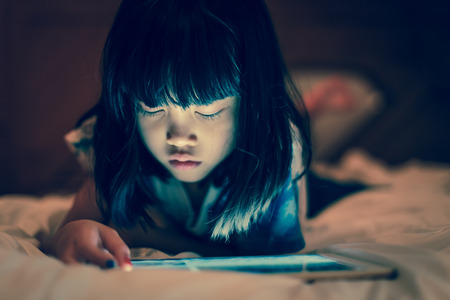 Kid using tablet for gaming and online learning while lying on the bed, in dim light bedroom background, screen light reflex on her face. Concept of internet technology, appropriate contents for kids. Stock Photo