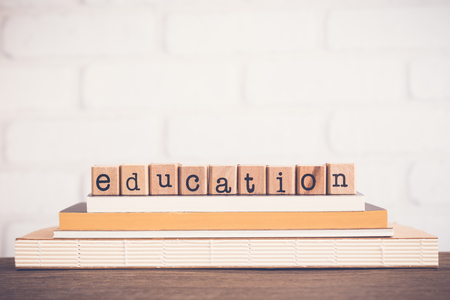 The word Education, alphabet on wooden rubber stamps on top of books and table. White bricks background, blank copy space, vintage and minimal style. School learning course, academic curriculum. Banco de Imagens