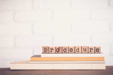The word Procedure, alphabet on wooden rubber stamps on top of books and table. Bricks background, blank copy space, vintage minimal style. Business management, manual process, document information.