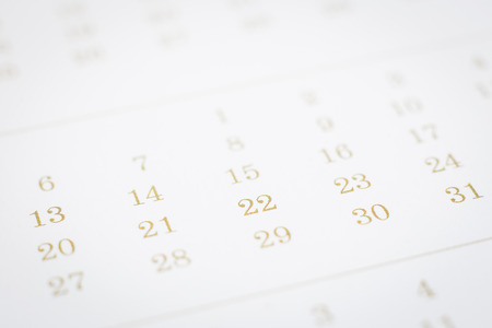 Selective focus on days and dates of calendar page. Closeup timetable shown mix dot prints for gold color. Modern schedule background clean minimal style. Project planning, appointment concepts.