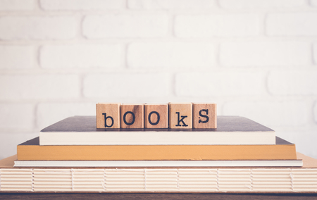 The word Books, alphabet on wooden cubes on top of books. Background copy space, vintage minimal style. Knowledge sources and education concepts for library club, school training courses or institute.