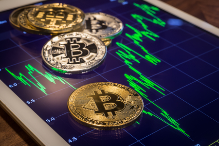 Cryptocurrency metal, focus gold bitcoin on tablet screen that showing green price or stock market performance graph. Concepts of decentralized, transfer or exchange digital money through blockchain.