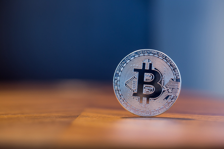 Cryptocurrency symbol electronic sign, focus on silver metal Bitcoin stack on wooden table, blur dark blue wall background copy space. Concept of transfer or exchange digital money through blockchain.