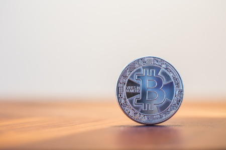 Cryptocurrency symbol sign, focus on silver metal Bitcoin stack on wooden table, blur white background copy space. Decentralized, transfer or exchange digital money through blockchain.