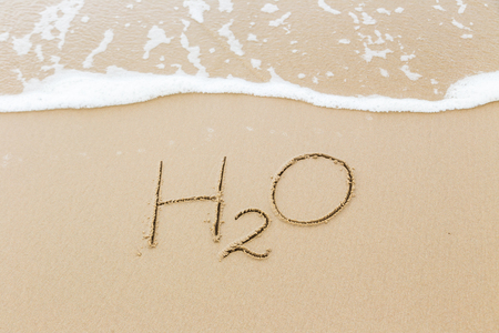 The word H2O written in sand beach with foam wave in background, Natural daylight in summer season. Texture, saving environment and water concepts. Archivio Fotografico