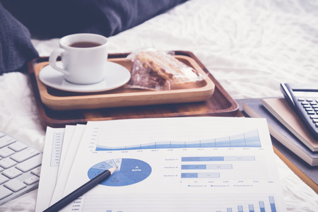 Blue summary chart, financial graphs, paperwork on wrinked duvet and bed. Tea break and pillows on background, natural daylight, soft vintage retro style. Concept of relax and freelance work at home. Reklamní fotografie