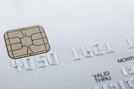 Carte de crédit à puce gris argent, gros plan avec une mise au point sélective sur les chiffres en relief, la puce électronique, le motif de points sur fond et l'espace de copie vierge blanc sur le dessus. Paiement, sécurité financière. Banque d'images