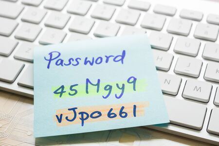 Handwriting passwords with highlight colors written on blue paper note on top of modern white keyboard with wooden office table on background. Login access, data privacy and cyber security concepts.
