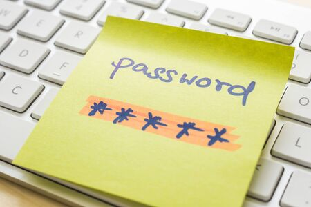 Secret password with highlight color written on yellow paper note on top of modern white keyboard with wooden desk on background. Login access, encryption and cyber security concepts. Reklamní fotografie