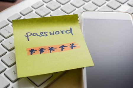 Secret password written on yellow paper note stick on blank black screen of mobile phone with modern white keyboard on background. E-commerce, internet banking, data privacy, cyber security concepts.