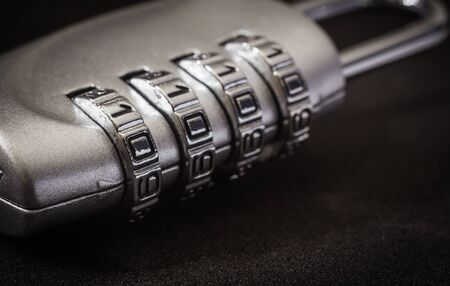 Close up 4 digits code number on silver combination padlock on black background, dim light dark tone. data protection, key management, password access, security encryption concepts. Banco de Imagens