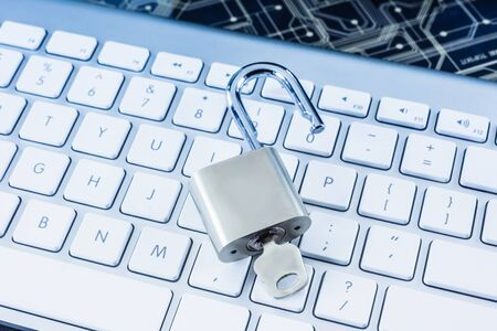 Unlock metal padlock with key on modern white keyboard, blue filter. Digital technology, encryption, internet access, cyber security, system login, business solution, future innovation concepts.