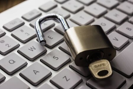 Open padlock with word SAFE on key on white pearl keyboard, dark tone with natural light reflect on objects. Cracking password, encryption, internet access, cyber network, data security concepts.