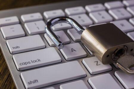 Ontgrendel hangslotsleutel op wit toetsenbord met tab, caps lock-knoppen, donker gedimd licht. Digitale gegevens, encryptie, cyberbeveiliging, informatieprivacy, bedrijfsoplossing, internetverbindingsconcepten. Stockfoto
