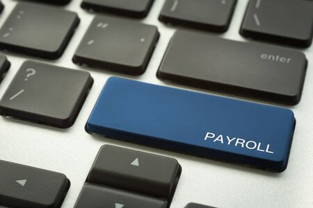 Close up blue button laptop keyboard selective focus on word PAYROLL. Human resources, salary, accounting, financial and business administration concepts.