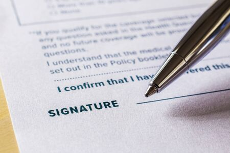 Close up word signature with pen on legal contract form. Policy document, registration, employment and business startup concept.