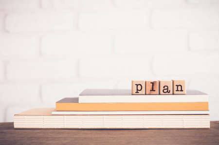 The word TIPS, letters on wooden block cubes on top of books and table with white bricks background,  blank copy space, vintage minimal style. Concepts of  tricks, hack, help, guideline, useful hint.