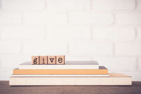 The word HELLO, letters on wooden rubber stamps on top of books with bricks background, blank copy space, vintage minimal style.  Concepts of communication, conversation, language, english greetings.