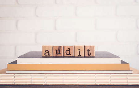 The word AUDIT, alphabets on wooden rubber stamps on top of books with bricks background, blank copy space, vintage minimal style. Concepts of examination, finance, accouting and business management.