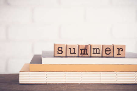 The word SUMMER, letters on block cubes on top of books and wooden table with white bricks background, blank copy space, vintage minimal style. Concepts of season, weather, holiday and lifestyle.