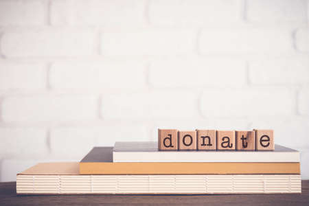 The word DONATE, alphabets on wooden rubber stamps on top of books with bricks background, blank copy space, vintage minimal style. Concepts of give, aid, help, share and charity.