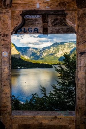 hallstatt lake view captured through the window of a wooden hut