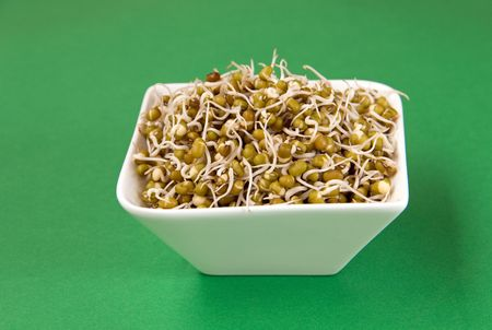 gram: bowl of green gram sprouts against green background